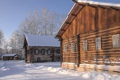 Old log houses in the village of frosty snowy winter.  stock photo
