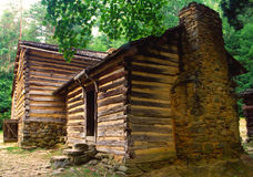 Old log pioneer home with a rock fireplace. Stock Photo