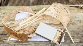 On the old log is situated a set of dry for kindling the campfire (birch bark, paper, shavings and matches) in a forest. On the old log is situated a set of dry royalty free stock images
