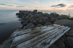 Old logs carved by water washed out on jetty. At sunset Royalty Free Stock Photography