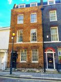 Old London Town House. An end of terraced old London town house with sash windows and sun burst front door window and iron railings outside by the pavement in Royalty Free Stock Photography