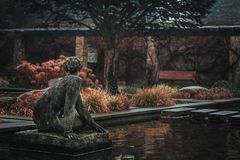 Old lonely concrete statue of a woman looking away. Surrounded by water in a park Stock Image