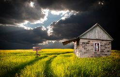 Old lonely house in a field and thunderclouds royalty free stock images