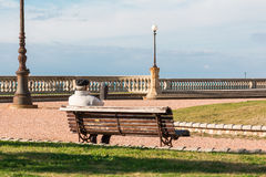 Old lonely man sitting on public bench, waterside Solitude Stock Image