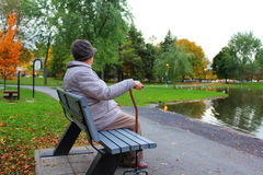 Old, lonely woman. Sitting on a bench in autumn scene Stock Image