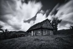 An old, long-abandoned house, against the background of a cloudy sky, shot on a long exposure. Abandoned house in West Ukraine.Old royalty free stock image