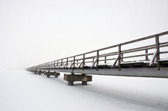Old long wooden bridge on winter lake snowy ice and fog Royalty Free Stock Photography