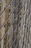 Old long wooden chain linked fence in the back. A old steel and wooden metal chain linked fence in the back warehouse area by the cans stock images