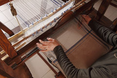 Old loom. A woman work on a hand loom stock image