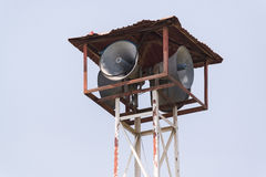 Old loudspeakers broadcast tower with a clear sky background. Old public loudspeakers broadcast on high tower with long distance tower on clear sky background Royalty Free Stock Images