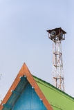 Old loudspeakers broadcast tower with a clear sky background. Old public loudspeakers broadcast on high tower with long distance tower on clear sky background Stock Photo