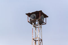 Old loudspeakers broadcast tower with a clear sky background. Old public loudspeakers broadcast on high tower with long distance tower on clear sky background Royalty Free Stock Photos