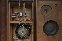Old Loudspeakers Repair. Damaged vintage loudspeakers repair, wooden wall in the background Stock Images