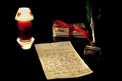 Old love letter. Antique quill, stack of letters tied with a red ribbon and romantic candle Stock Photos