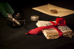 Old love letter. Love letter, antique quill and black ink and stack of letters tied with a red ribbon Royalty Free Stock Photo