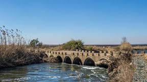 Low water bridge with a gabion retaining wall. Old low water concrete bridge with a modern gabion retaining wall to control erosion image with copy space in royalty free stock photo