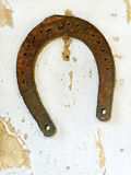 Old lucky horseshoe on aged white clay wall background. Royalty Free Stock Images