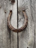 Old lucky shoe. An old Rusty horseshoe hanging on a barn wall Royalty Free Stock Photography