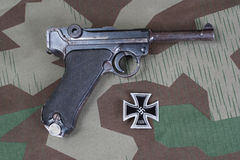 Luger Parabellum handgun and medal Iron Cross on camouflaged background Royalty Free Stock Image