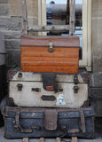 Old luggage trolley. Two old suitcases and a trunk waiting on a trolley on a platform Stock Photos