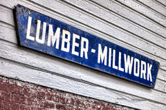 Old Lumber Millwork Enamel Sign on Building Wall. Old and distressed lumber millwork antique advertising enamel sign hanging on a vintage lumberyard wood Stock Image
