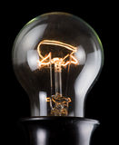 Old luminescent electric lamp on black Stock Photos