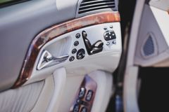 Old luxury modern car interior, beige color, electronic buttons, automatic transmission lever.  royalty free stock image