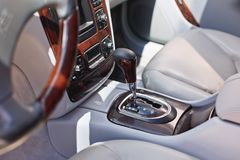 Old luxury modern car interior, beige color, electronic buttons, automatic transmission lever.  royalty free stock photography