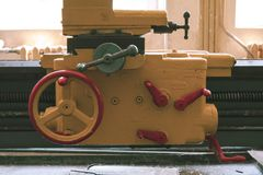 Old machine in an abandoned factory retro picture. Gray vintage machine with red handles. Workplace at an old abandoned factory. close-up control levers in the stock photos
