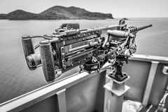 Old machine gun on side of the warship Stock Photo