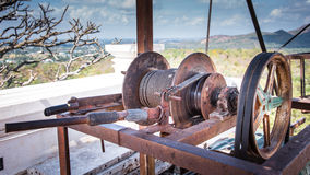 An old machine including reel , belt and basket. Aged by time and cover with rust. Stock Image
