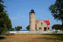 Old Mackinac Point Lighthouse. Exterior of Old Mackinac Point Lighthouse on coastline of Lakes Huron and Michigan in background, U.S.A Royalty Free Stock Photo