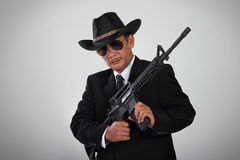Old mafia and his assault weapon. An old mafia in black suit and cowboy hat posing with an assault weapon Stock Photos