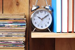 Old magazine, clock, books on wooden shelf Royalty Free Stock Photo