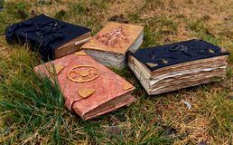 Old magic books on grass background. Occult, esoteric, divination and wicca concept. Mystic and vintage background with old objects royalty free stock images