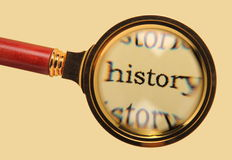 Old magnifying glass on word history. Old magnifying glass enlarged word history Stock Photos