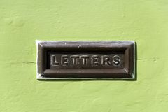 Snail mail. Old mail letter box in a distressed green house front door Stock Photos