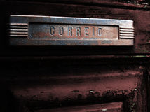 Old mail slot in old door. A view of an old and rusty mail slot on an equally old door. In the plate is engraved the Portuguese word correio (mail Royalty Free Stock Photo