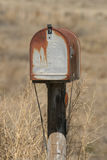 Old mailbox. Next to a prairie dust road with gunshot hole in it Royalty Free Stock Photos