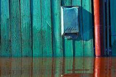 Old mailbox and flood. Fence of the rural house during a flood stock photography