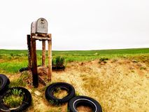 Old mailbox in the middle of nowhere. Old mailbox surrounded by old tires in the middle of nowhere Stock Images