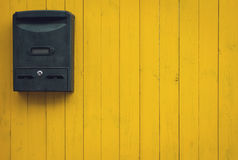 Old mailbox on a yellow wooden background Stock Image