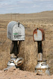 Old mailboxes. Next to a prairie dustroad with gunshot hole in it Royalty Free Stock Photos