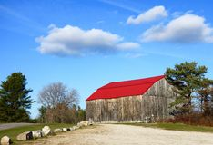 Old Maine country barn, bright red roof, blue sky Royalty Free Stock Photo