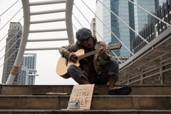 Old beggar play guitar in city to get donate. Old male beggar or Homeless dirty man playing guitar on stair of modern city with donate bowl, paper cardboard with royalty free stock photos