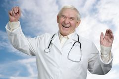 Old male doctor laughing out loud with hands up. Happy senior physician with stethoscope wearing white lab coat. Blue sky background Royalty Free Stock Images