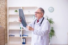 Free Old Male Doctor Radiologist Working In The Clinic Royalty Free Stock Images - 197420769