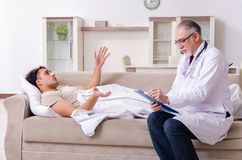 Old male doctor visiting young male patient. The old male doctor visiting young male patient royalty free stock photo