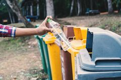 Old male hand throwing empty plastic bottle. Into the trash Royalty Free Stock Image