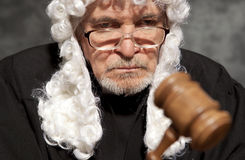 Old male judge in a courtroom striking the gavel Royalty Free Stock Images